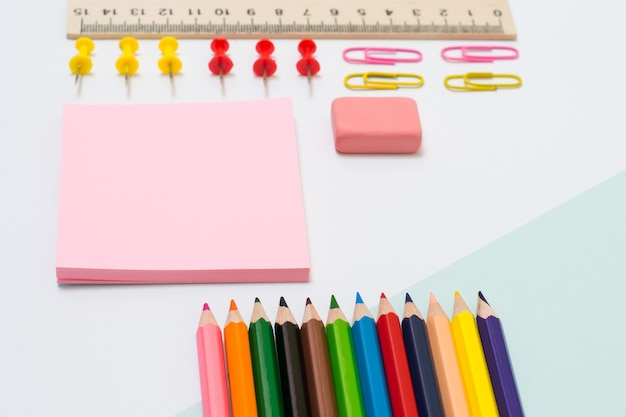 Set di materiale scolastico. vista dall'alto foto ravvicinata di matite colorate, adesivi, graffette e spilli, gomma, righello su sfondo bianco