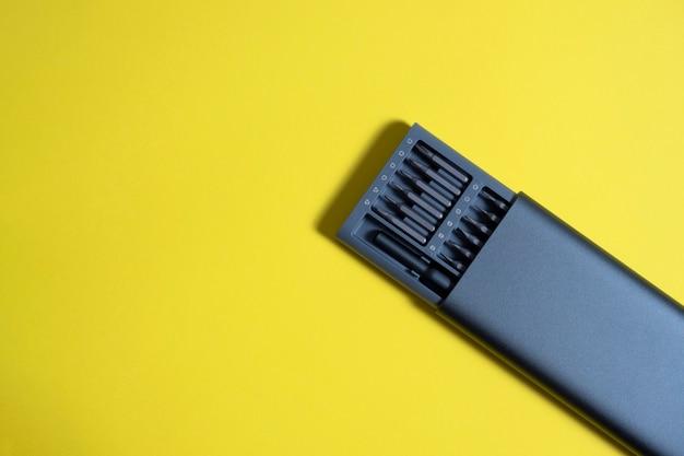 Un set di cacciaviti con punte in una custodia su sfondo giallo. copyspace, strumenti per il lavoro