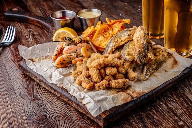 Set frutti di mare: cozze, gamberetti, piccolo pesce di mare fritto, cracker e salse, cibo che di solito viene servito con birra, orientamento orizzontale, primo piano