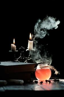 Set di libro di stregoneria, pozione magica e candele sul tavolo