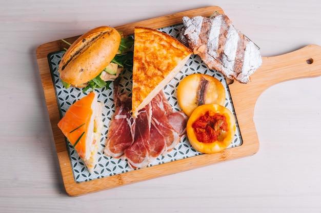 Set di colazione spagnola per la consegna frittata con patate panino al prosciutto iberico su una tavola di legno
