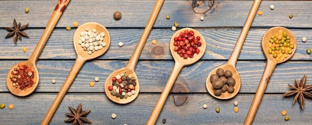 Set di miscele di spezie in cucchiai di legno sul tavolo di legno scuro.