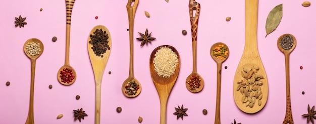 Set di miscele di spezie in cucchiai di legno su sfondo rosa.