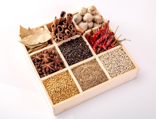 Set di spezie (pepe, pepe bianco, pepe nero, anice, cumino,) in una scatola di legno.