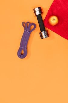 Set di accessori sportivi rullo massaggiante, imbracatura sportiva, cuffie su sfondo giallo