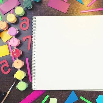 Set di elementi decorativi per notebook scolastico sdraiato sul tavolo vista dall'alto copia spazio concetto di ritorno a scuola