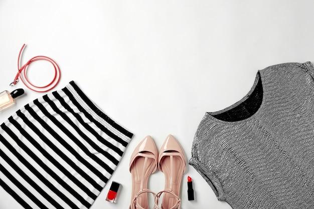 Set di vestiti alla moda e cosmetici per donna su sfondo bianco