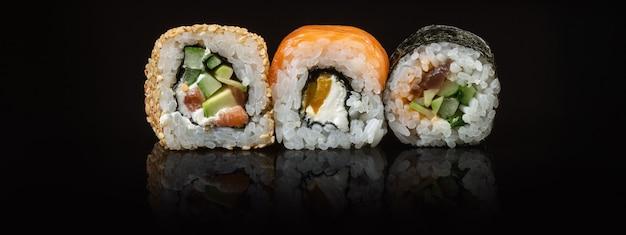 Set di rotoli di sushi e maki sul tavolo di vetro con riflesso
