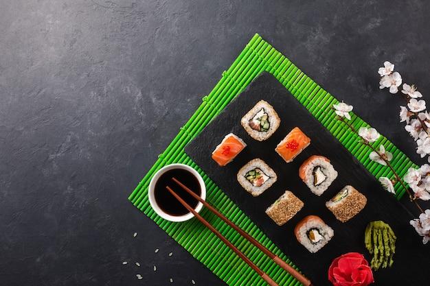 Set di rotoli di sushi e maki con ramo di fiori bianchi sul tavolo di pietra. vista dall'alto.