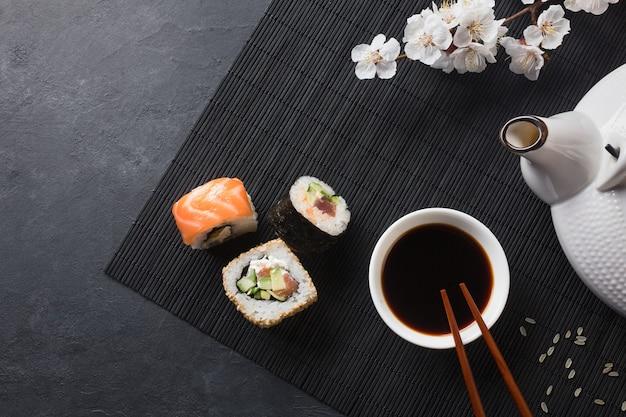Set di rotoli di sushi e maki con ramo di fiori bianchi e teiera sul tavolo di pietra. vista dall'alto.
