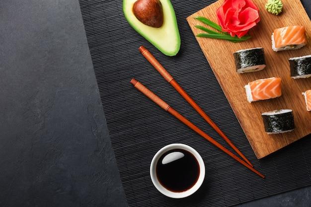 Set di rotoli di sushi e maki con avocado a fette sul tavolo di pietra. vista dall'alto.