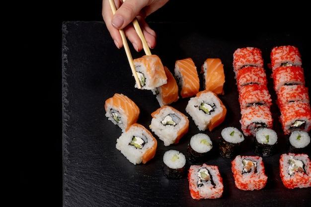 Set di rotolo di sushi su sfondo nero ardesia cibo pesce philadelphia salmone giapponese delizioso sushi riso cetriolo pasto tradizionale wasabi fresco sano gourmet cucina cruda
