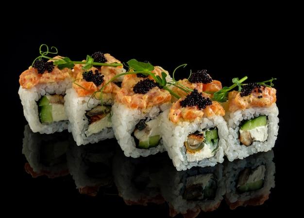 Impostare il rotolo di sushi. cucina tradizionale giapponese. isolato su sfondo nero. roll con salmone, cetriolo e anguilla affumicata