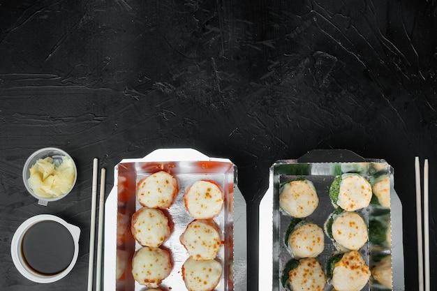 Set di rotoli di sushi in scatola per alimenti per la consegna, su sfondo di pietra nera, vista dall'alto piatta, con copyspace e spazio per il testo
