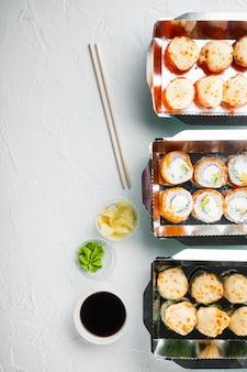 Set di rotoli di sushi in scatola per alimenti per la consegna, su pietra bianca