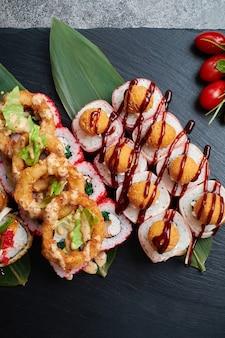 Set di rotoli di sushi si trova su foglie di bambù con lime, erbe aromatiche e pomodori rossi, servito su una pietra nera ardesia.