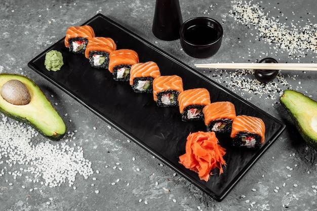 Una serie di involtini di sushi philadelphia con pesce rosso, crema di formaggio e riso nero si trova in una barca a piastra. rotoli di sushi su uno sfondo grigio.