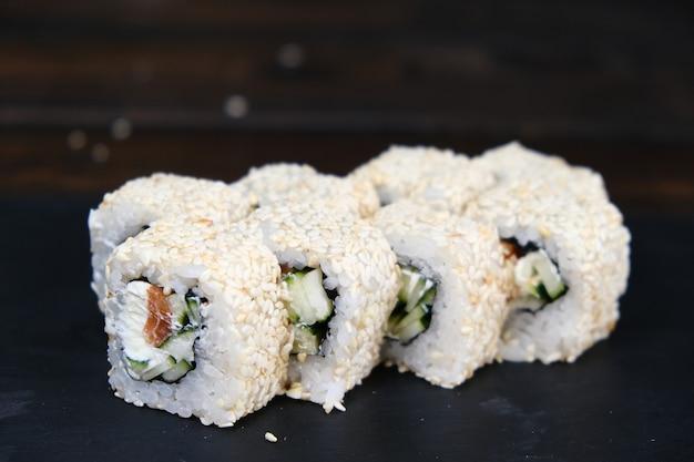 Set di involtini di sushi con tonno, salmone, cetriolo, avocado su una tavola nera. primo piano, profondità di campo. assortimento di cibo giapponese nel ristorante.