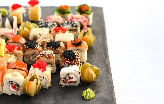 Set di rotoli di sushi con vasabi e zenzero su un piatto di ardesia scura, tavolo da buffet, orientamento orizzontale, primo piano, spazio di copia