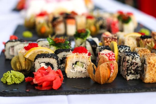 Set di rotoli di sushi con vasabi e zenzero su un piatto di ardesia scura, tavolo da buffet, orientamento orizzontale, primo piano