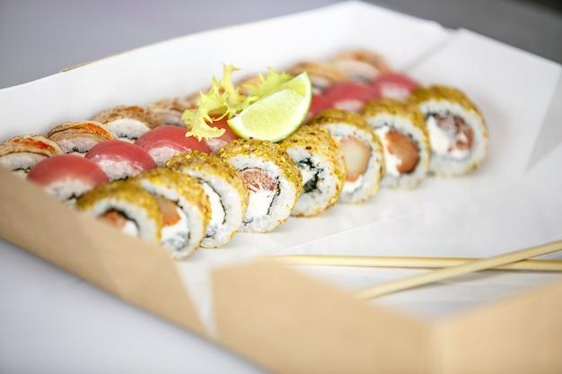 Set di sushi, set di sushi, sushi giapponese, insalata, zenzero, wasabi, in una scatola, su una superficie bianca con bacchette