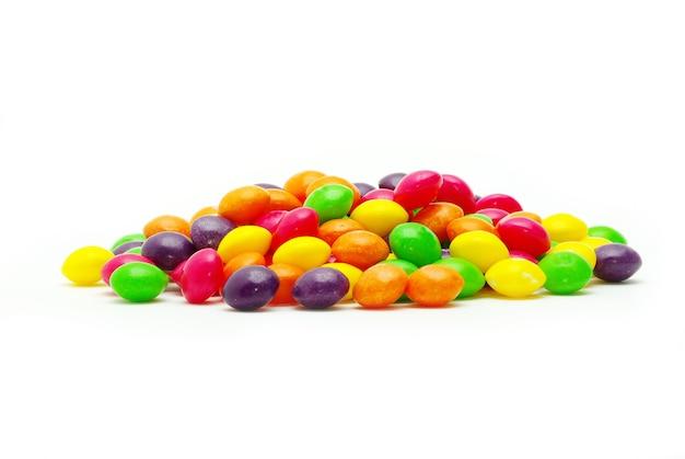 Set di dolci confetti di colore diverso su sfondo bianco
