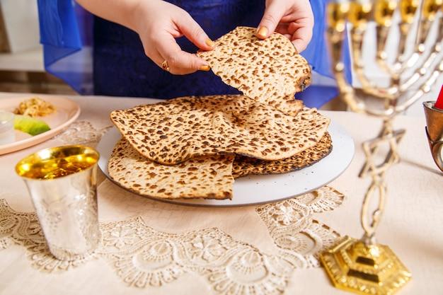 Apparecchiare la tavola per il seder pasquale con candele e matzah nelle mani della donna. foto orizzontale