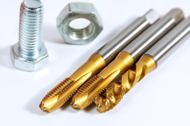 Set di maschi per filettare in metallo. bulloni e dadi isolati su sfondo bianco. strumento per la lavorazione del metallo.