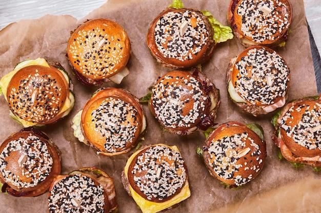 Set di gustosi cheeseburger in una scatola di legno su uno sfondo chiaro. una scatola con diversi hamburger, un'offerta fissa per un'azienda,