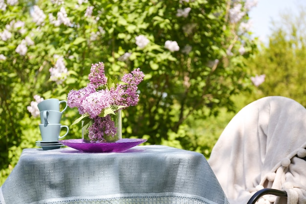 Set di tazze da tè e bellissimi fiori lilla sul tavolo all'aperto