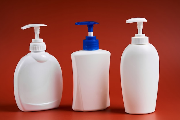 Set di tre bottiglie di plastica bianche pulite con distributore di sapone