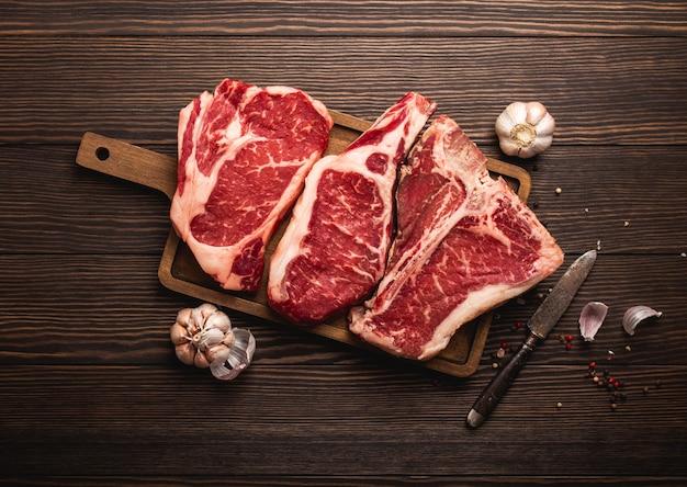 Set di tre diversi tipi di bistecche di carne cruda: ribeye, t-bone, cowboy su tagliere con coltello e condimenti, fondo in legno. assortimento di bistecche invecchiate, concetto di macelleria/ristorante, vista dall'alto, primo piano