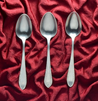 Un set di tre cucchiai di metallo su una tovaglia di seta rossa. vista dall'alto.