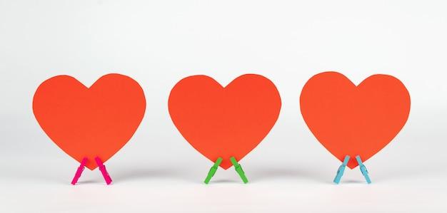 Un insieme di tre cuori di carta sta sulle mollette da bucato di legno su fondo bianco. minimo concetto di amore.