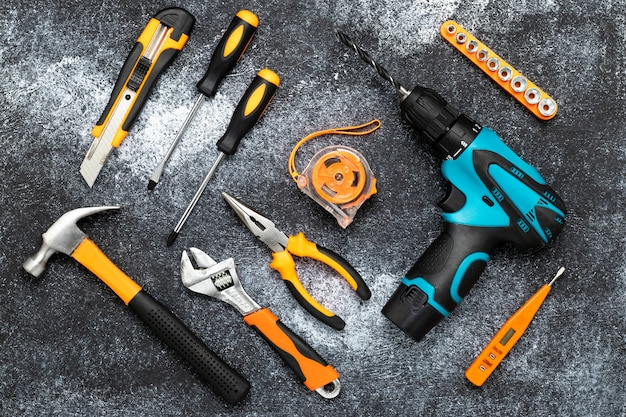 Una serie di strumenti per la ristrutturazione della casa, una raccolta di strumenti su una superficie nera. concetto fai da te.