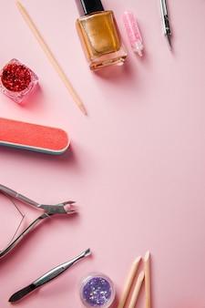 Un set di strumenti per manicure e cura delle unghie su un rosa