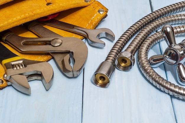 Set di strumenti in borsa e tubo in pelle scamosciata su lavagne blu