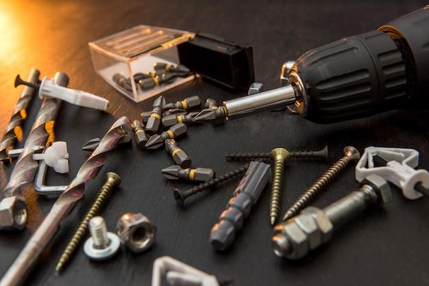 Set di strumenti sul tavolo, un cacciavite con un set di punte da trapano e viti con bulloni. tutto da riparare