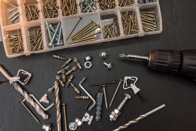 Set di strumenti sul tavolo, un cacciavite con un set di punte da trapano e viti con bulloni. tutto per la riparazione