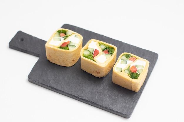 Set di tortilla roll con verdure sono serviti su una tavola di ardesia nera