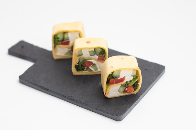 Set di involtini di sushi tortilla con verdure servite su una tavola di ardesia nera.