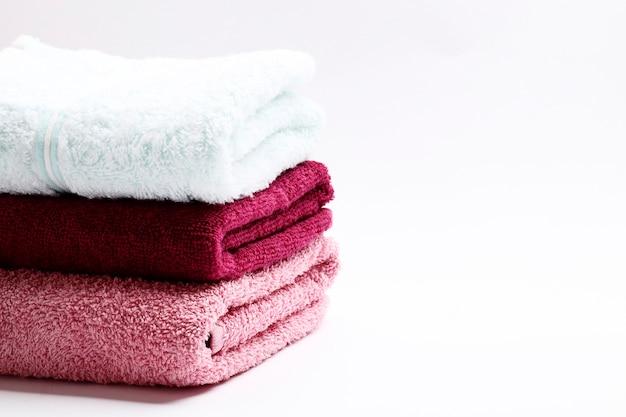 Un set di asciugamani di diversi colori su uno sfondo bianco. posto per il testo