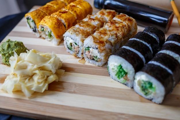Set di piatti tradizionali giapponesi. involtini di sushi, nigiri, salmone crudo, riso, crema di formaggio, avocado, zenzero sottaceto.
