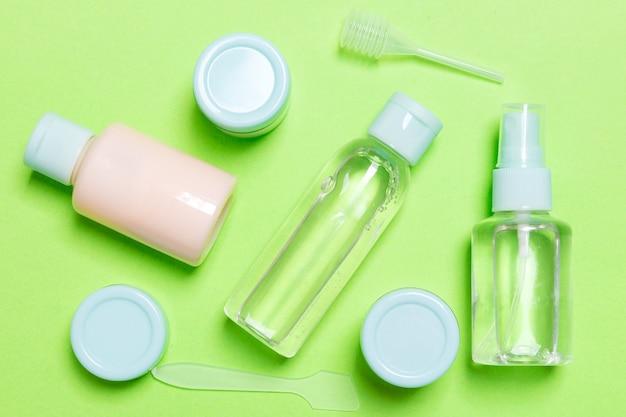 Set di flaconi per la cosmetica da viaggio su sfondo verde. lay piatto di vasetti di crema. vista dall'alto del concetto di stile per la cura del corpo.