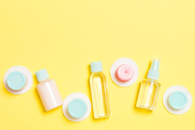 Set di flaconi per la cosmetica da viaggio su sfondo giallo. lay piatto di vasetti di crema. vista dall'alto del concetto di stile per la cura del corpo.