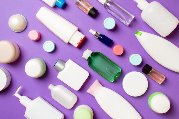 Set di contenitori cosmetici da viaggio su sfondo viola