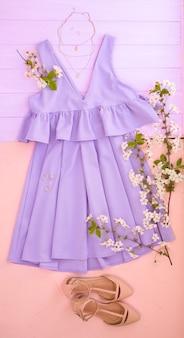 Set di abiti femminili alla moda, accessori e rami fioriti su sfondo colorato