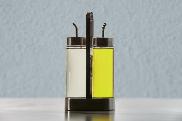 Set di due bottiglie per olio o aceto con beccuccio erogatore in un supporto in metallo.