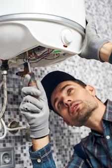 Installa il lavoratore della caldaia installa la caldaia per il riscaldamento elettrico nel bagno di casa