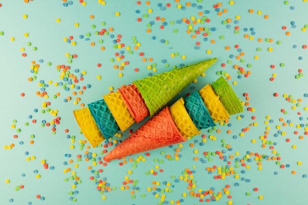 Insieme di vari coni di cialda gelato multicolori luminosi con confetti sparsi zucchero spruzza.